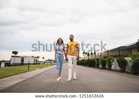 Cheerful twosome is walking down the street. They looking ahead with smile. Copy space. Alley on background