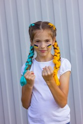 cheerful Ukrainian girl with blue and yellow hair shows her strength. sport and fan support concept. patriotism and independence of Ukraine.