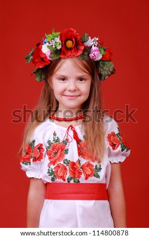 Cheerful ukrainian little girl over bright red background/Smiley face of lovely kid