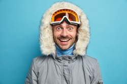 Cheerful unshaven man with overjoyed expression smiles broadly wears ski goggles winter jacket with hood enjoys extreme winter sport poses against blue background. Snowboarding hobby concept