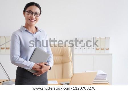 Cheerful Vietnamese school director in her office #1120703270
