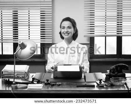 Cheerful vintage secretary working at office desk and smiling at camera