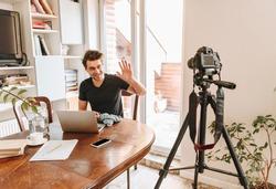 cheerful vlogger knitting and waving hand while looking at digital camera on tripod