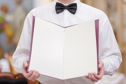 Cheerful waiter. Cropped image of handsome young waiter in shirt and bow tie holding a menu with blank pages for copy space in the luxury restaurant