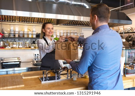 Cheerful waitress wearing apron serving customer at counter in restaurant - Small business and service concept with young business owner woman giving bag with takeaway food to client