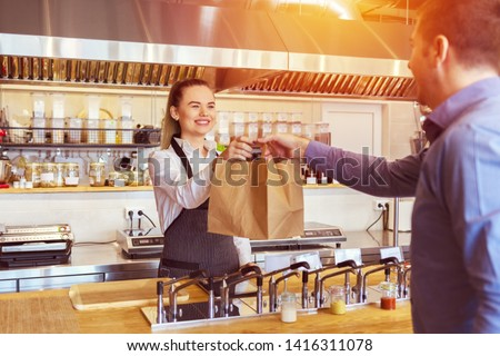 Cheerful waitress wearing apron serving customer at counter in restaurant - Small business and service concept with young woman owner offering recycled paper bag with take away food to online client