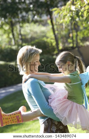 Cheerful woman carrying daughter in tutu enjoying at park