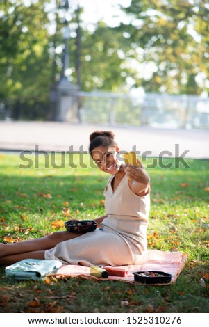 Cheerful woman. Cheerful woman holding yellow smartphone while making selfie having little picnic #1525310276
