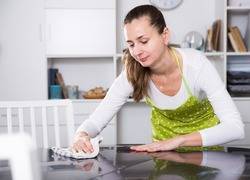 Cheerful woman doing housework - washing kitchen table with rag