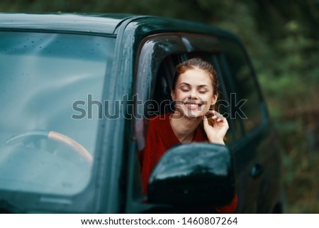 Cheerful woman driving a car trip countryside countryside lifestyle of nature