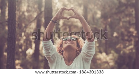 Photo of  Cheerful woman enjoy nature and outdoors natural forest doing hearth sign with hands and smiling to trees - concept of save nature world and environment lifestyle people