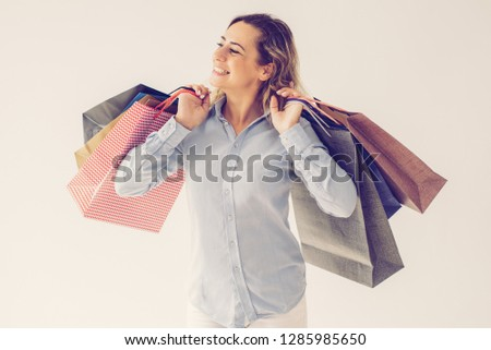 Cheerful woman enjoying shopping and carrying many bags. Happy dreamy beautiful lady with curly hair spending money. Consumerism concept