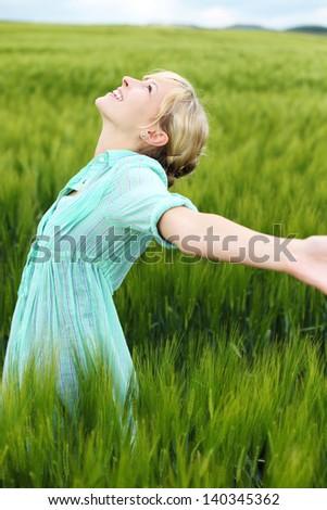 Cheerful woman enjoying the fresh air in cornfield