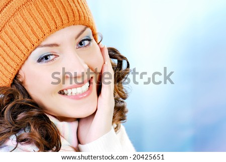 Cheerful woman face clothing in warm orange hat. Winter season.