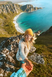 Cheerful woman follow holding hand her boyfriend couple travel vacations friends having fun outdoor hike tour in Norway adventure lifestyle aerial view ocean beach