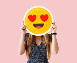Cheerful woman holding emoticon icon