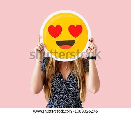 Cheerful woman holding emoticon icon #1083326276