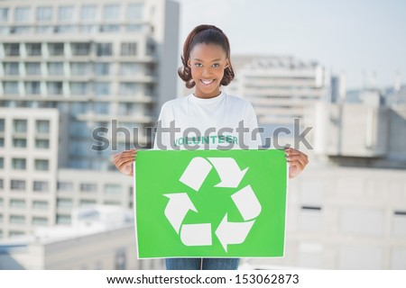 Cheerful woman holding recycling sign outdoors on urban background