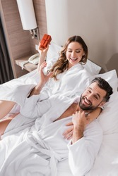 Cheerful woman in bathrobe holding gift box and hugging boyfriend on hotel bed
