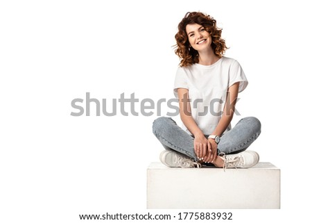 cheerful woman in jeans sitting on cube and smiling isolated on white Photo stock ©