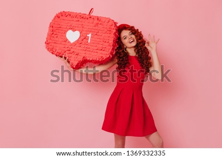 Cheerful woman in minimalistic red outfit smiles and shows OK sign. Girl in beret holds like sign on pink background