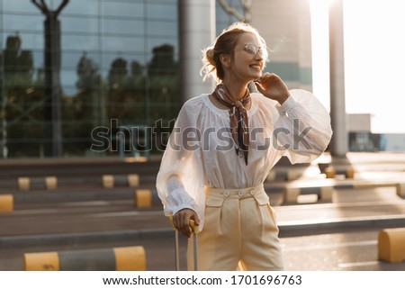 Cheerful woman in stylish blouse and beige pants smiles widely. Attractive blonde girl in white shirt poses with luggage near airport.
