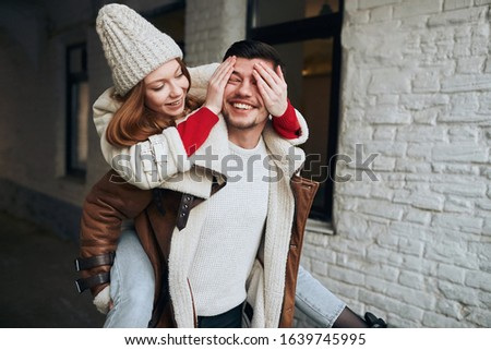 cheerful woman in stylish cap and coat closing her man's eyes with palms, happiness, flirt, affection, surprise.
