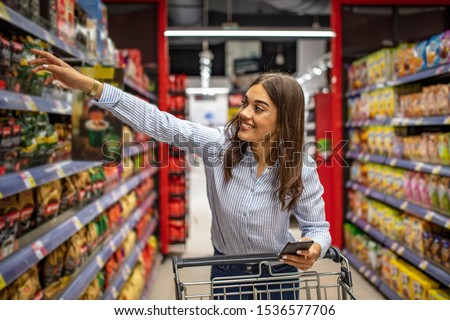 Cheerful woman in supermarket with shopping trolley choosing products and using phone. Looking aside. The housewife chooses food for dinner at home on the background of shelves in a supermarket.