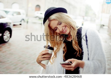 Cheerful woman in the street drinking morning coffee and use her smartphone. #483628468