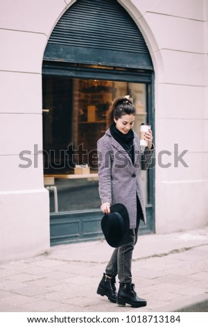 Cheerful woman in the street drinking morning coffee to go. Girl in a coat, scarf and hat. Woman drinking coffee and laughing. Vacation, weekend, takeaway drinks, leisure concept.