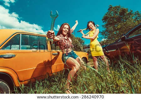 Cheerful woman mechanic is repairing a car with the wrench another woman is watching.