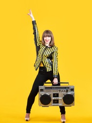 Cheerful woman on a yellow background. Girl with a retro tape recorder. The woman is dancing. Disco dance. Positive mood.