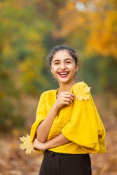 Cheerful woman portrait with autumn maple leaves in the park