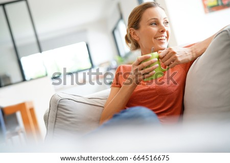 Cheerful woman relaxing in sofa and drinking tea #664516675