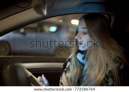 Cheerful woman riding car as passenger and browsing tablet
