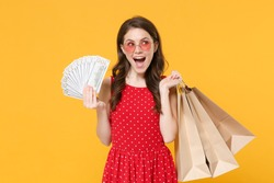 Cheerful woman 20s in red summer dress, eyeglasses isolated on yellow background. People lifestyle concept. Hold package bag with purchases after shopping, hold fan of cash money in dollar banknotes