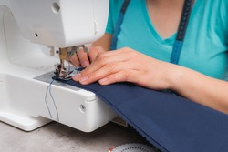 Cheerful woman sewing while sitting at her working place in fashion workshop