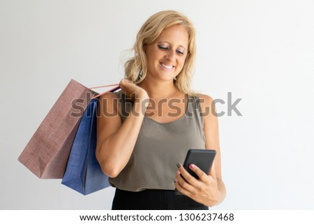 Cheerful woman shopping online. Smiling pretty woman making purchases via smartphone application. Consumerism concept