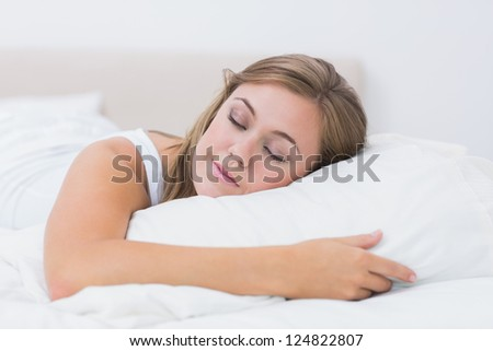 Cheerful woman sleeping in white bedroom at day