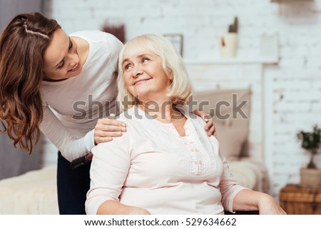 Cheerful woman taking care of her grandmother in wheelchair