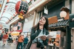 Cheerful woman traveler with camera holding a guidebook travel in japan. osaka travel concept. Happy tourist indoor market in sunny city centre in Japan.Translation of lantern texting