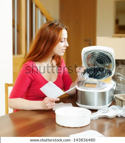 cheerful woman unpacking and reading manual for new crockpot at home interior