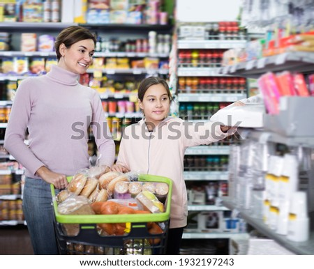 Cheerful woman with girl shopping with shopping cart in supermarket Stock fotó ©