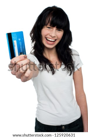 Cheerful woman with long hair displaying her cash card to you.