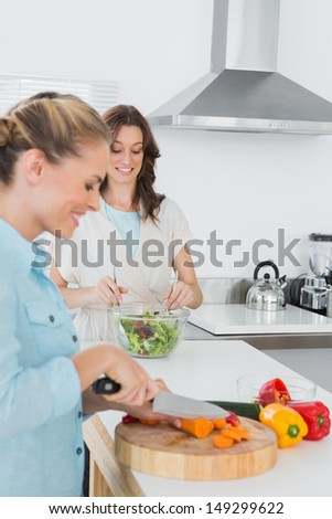 Cheerful women cooking together in the kitchen