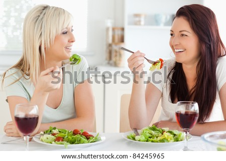 Cheerful Women eating salad in a kitchen
