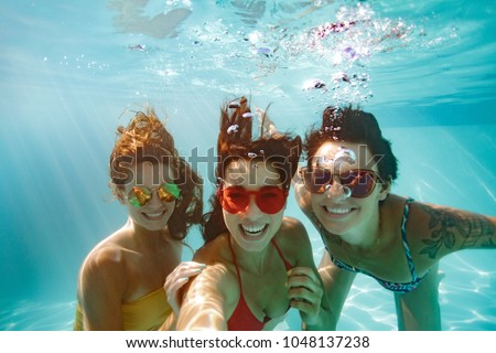 Cheerful women friends swimming underwater in pool taking selfie. Underwater selfie of happy females in pool.