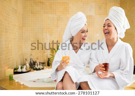 Cheerful women in bathrobes drinking juice: friends in spa salon