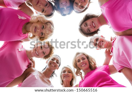 Cheerful women smiling in circle wearing pink for breast cancer on white background