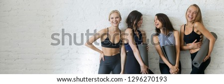 Cheerful women wearing activewear standing near wall hold yoga mats ready start fitness training sportive healthy wellbeing lifestyle concept, banner for website header design with copy space for text